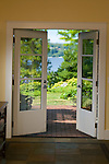 Skewed-focus detail shot of a pair of French doors leading to a brick patio, a sunny pocket garden, and views of the water from this waterfront weekend vacation retreat on Washington State's Vashon Island.