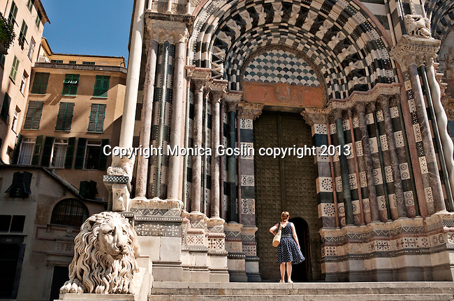 Facade, steps, marble lion of the St Lawrence Cathedral in Genoa, Italy with a lady in a navy polk-a-dot dress going into the Cathedral