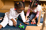 Preschool ages 3-5 two girls playing together in block area horizontal playing with human figures and vehicles horizontal