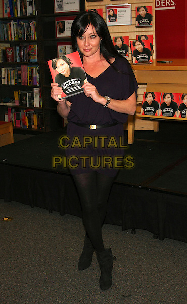 SHANNEN DOHERTY.'Badass' book signing at Borders, Columbus Circle, New York, NY, USA 2nd November 2010.full length black dress belt tights holding  purple ankle boots .CAP/LNC/TOM.©TOM/LNC/Capital Pictures.