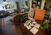 NWA Democrat-Gazette/ANDY SHUPE<br /> Cat Rosenschein, executive director of Compassion House in Elm Springs, sorts through a bag of donated children's books Friday, June 29, 2018, at Compassion House in Elm Springs. Sade Danie is the first 18-year-old woman to move into Compassion House, a home for pregnant teens, after a policy change made June 11 allowed them to accept 18- and 19-year-olds.
