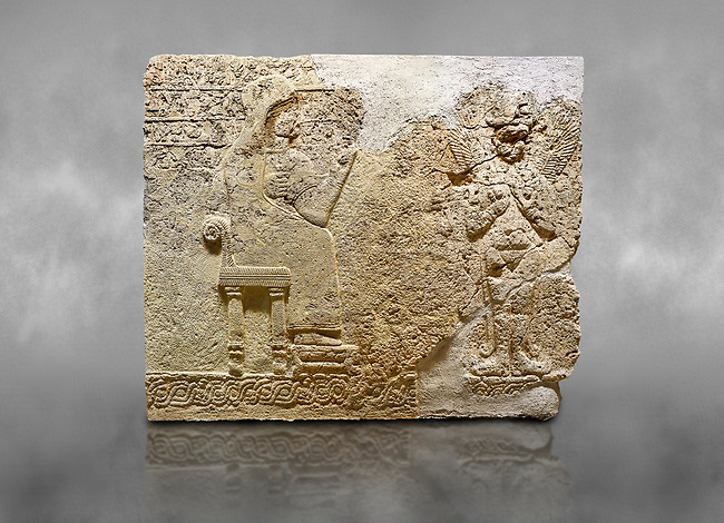 """Hittite relief sculpted orthostat stone panel  of Long Wall Limestone, Karkamıs, (Kargamıs), Carchemish (Karkemish), 900-700 BC. Anatolian Civilisations Museum.<br /> <br />  The hieroglyphics reads; """"I am Win-a-tis, beloved wife of my Lord Suhi, wherever and whenever my husband honours his name, he will honour my name as well with favours"""". Underneath, there are two goddess figures, one is naked with a horned head, holding her breasts with her hands. Her genitalia is indicated by a triangle. <br /> <br /> On a grey art background."""