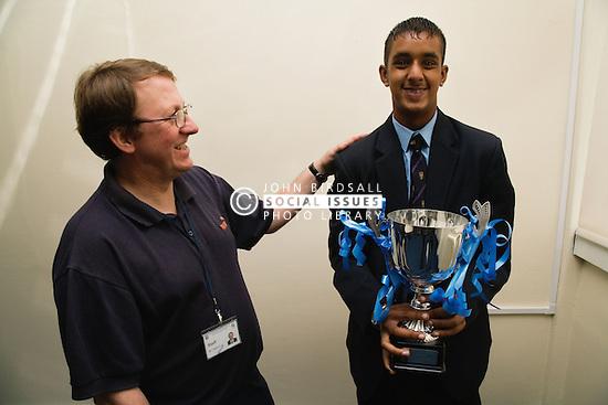 Teacher congratulating secondary school student on winning a prize,