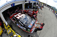 Tony Stewart (#14) backs out of his garage.