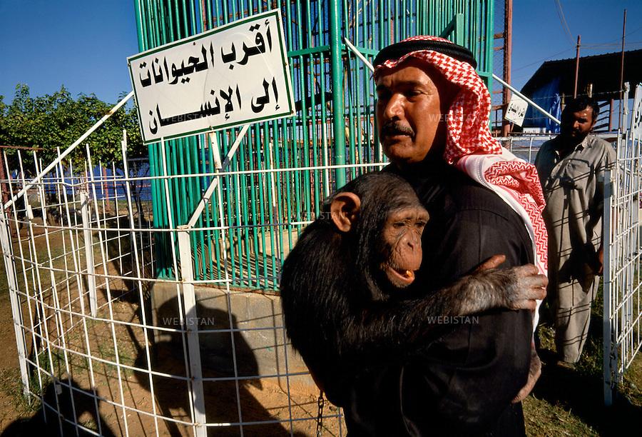 """2002. At the Unaizah zoo, a man holds a monkey in front of a cage with a sign saying: """"the animal the closest to the man."""" Au zoo d'Unaizah, un homme porte un singe près d'une cage dont l'écriteau dit: """" l'animal le plus proche de l'homme. """""""