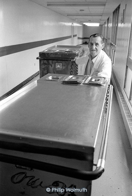 Kitchen porter with trolleys at Musgrave Park Hospital, Belfast.