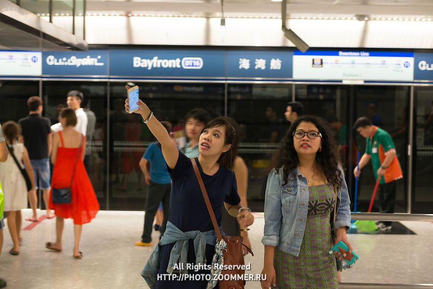Two women in Singapore Bayfront Subway station pointing to the map