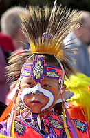 YOUNG CREE INDIAN WITH HIS FACE PAINTED AND DRESSED IN TRADITIONAL COSTUME IN REGINA, CANADA