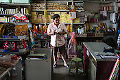 61 year old Lay Kee Tee, a former pig farmer and a  survivor of the Nipah virus stops to buy cigarettes at a shop in Bukit Pelandok in Nageri Sembilan, Malaysia on October 16th, 2016. <br /> In September 1998, a virus among pig farmers (associated with a high mortality rate) was first reported in the state of Perak in Malaysia. Dr. Chua investigated and discovered the virus and it was later named, Nipah Virus. The outbreak in Malaysia was controlled through the culling of &gt;1 million pigs.