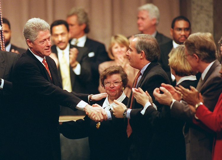 """After his speech, President Bill Clinton shakes hands with Sen. Robert Torricelli, D-N.J.,  as Sen. Barbara Mikulski, D-Md., and other House and Senate Democrats look on at the close of an hour-long tribute to their party's legislative achievements, particulary the enactment of the 1993 budget and tax package without Republican support. They also announced their """"unified legislative agenda for 1998,"""" on Feb 12, 1998. (CONGRESSIONAL QUARTERLY/SCOTT J. FERRELL)"""