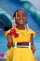 AFRICAN-AMERICAN GIRL (6) HOLDING A FLOWER LAUGHING PORTRAIT. 6 YEAR OLD GIRL. ORLANDO FLORIDA.