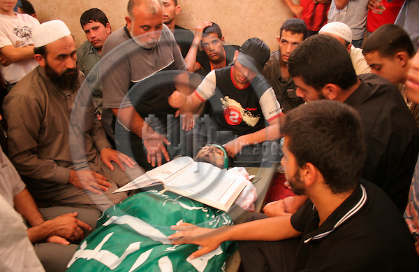 GAZA CITY - GAZA - 22 AUGUST 2007 -- Mourners sit next to the body of Yehya HABIB, a Hamas militant, during his funeral in Gaza. -- PHOTO: EUP-IMAGES / Thair ALHASSANY