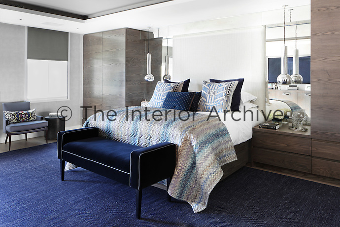 Built-in cupboards and mirrors flank the double bed which is dressed with Art Deco style cushions and a multi-coloured throw
