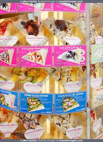 Fake food replicas, Sampuru in window display showing crepes, food stand menu in Tokyo, Japan.