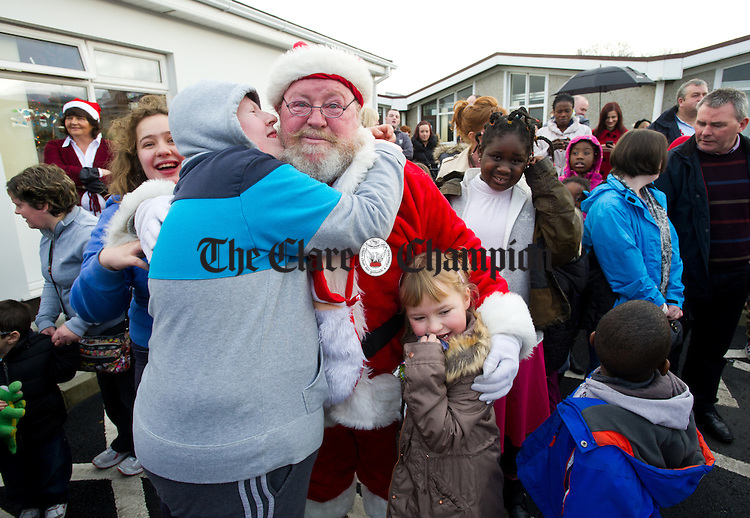 A delighted Sean O Connor and Emma Pilkington with Santa after he presented a cheque to the value of €5000 on behalf of the Mid West Bikers during their visit to St Anne's school on Saturday. Photograph by John Kelly.