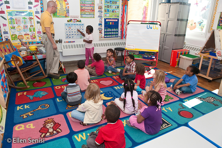 MR / Schenectady, New York. Fulton Early Childhood Education Center (urban public school early childhood education center). Pre-K classroom. Teacher and class at daily morning meeting look at calender and determine the date. This repetitive activity helps children learn days of the week, month, and year. Student (girl, 5) has a turn to stand in front of the class and help lead the activity. ID: AI-gPd. MR: Del17, Cal10 ©Ellen B. Senisi