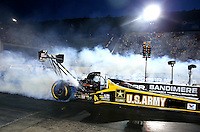 Jul. 18, 2014; Morrison, CO, USA; NHRA top fuel driver Tony Schumacher does a burnout during qualifying for the Mile High Nationals at Bandimere Speedway. Mandatory Credit: Mark J. Rebilas-