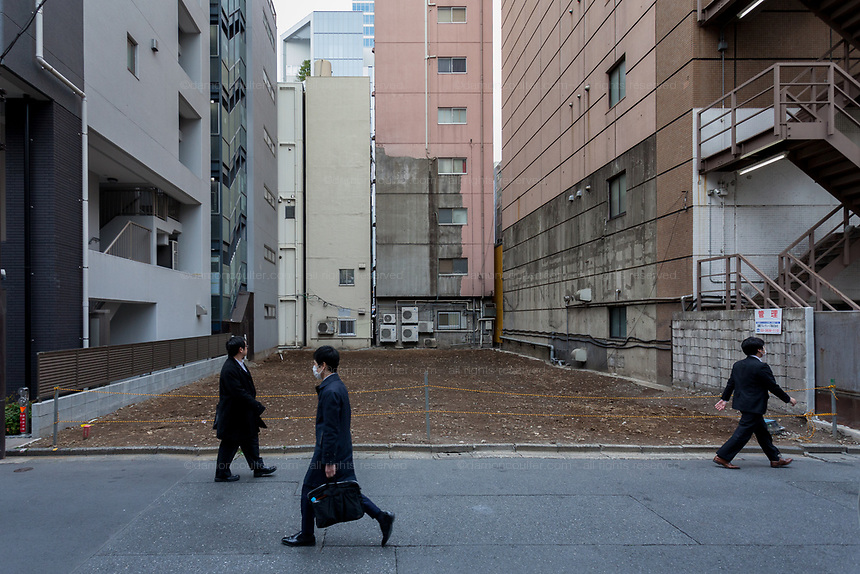 Three salarymen or male office workers walk past an empty lot that will be redeveloped in Akihabara, Tokyo, Japan. Monday April 1st 2019
