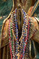 Rosary beads draped on the praying hands of a Blessed Mother statue at a Catholic shrine.