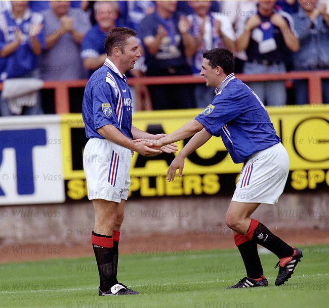Charlie Miller kneels before goalscorer Alistair McCoist MBE after the Rangers legend scored four goals in the match.
