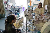 Staff nurse Regina Pezanowski cares for a patient while the mother looks on in the Neonatal Intensive Care Unit at Boston Children's Hospital in Boston, Mass., on Mon., June 13, 2016. Patient space, family space, and work space is all crowded together in the current NICU. The NICU will be greatly expanded under building plans for the hospital, but those plans will eliminate the Prouty Garden, a half-acre of green space at the hospital that many in the hospital community hold dear.