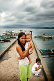 PHILIPPINES, Palawan, Puerto Princesa, mother with her baby in front of fishing boats at Liberty Fishing Village