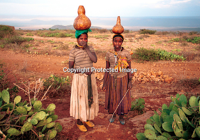 dicoeth00070.Ethiopia. Young girls carrying pots with water from a water hole on February 8, 2001 in Erer Valley in rural eastern Ethiopia. In this primarily muslim area, a project against Female Genital Mutilation (FGM) has made success in several rural villages in this area in stopping the practice. .©Per-Anders Pettersson/iAfrika Photos