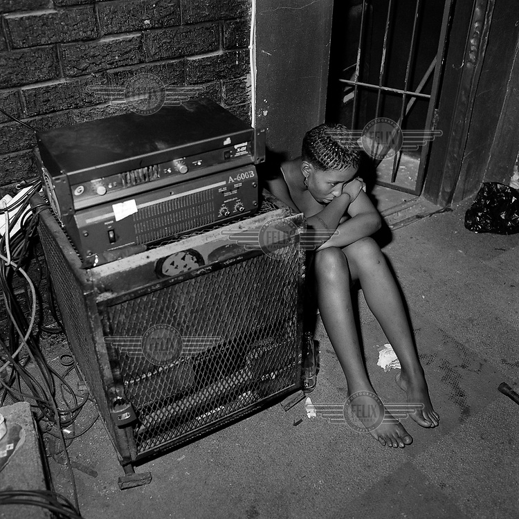 Lerato sits on the floor of the DJ booth in The Mexican Sports Bar, Hillbrow.