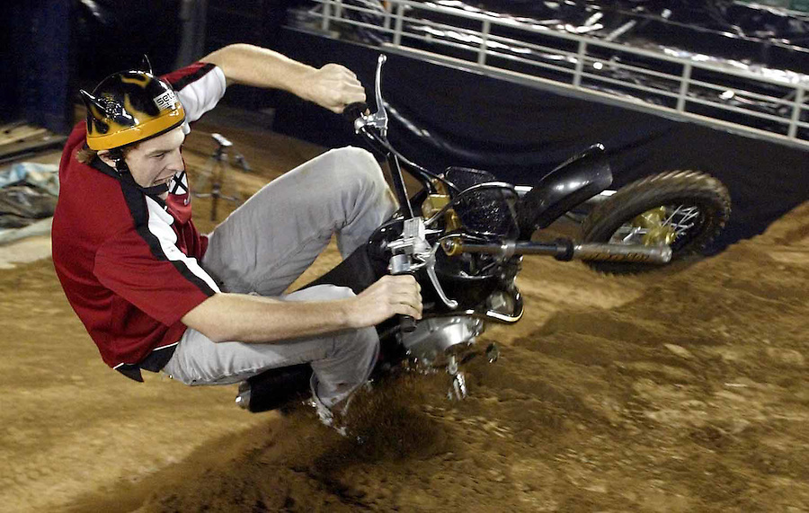 """St Kilda's Brendan Goddard took some time out of his preparation to get an up close look at dirt bike stunt jumpers the """"crusty demons"""" as they set up for their Melbourne show at Rod Laver Arena. Goddard came to grief attempting to emulate the crusty demons on a mini bike."""