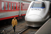 A worker walks past a new high-speed train at the rail station in Shanghai, China. The rail authorities introduced the high-speed trains as a measure to ease the pressure on the nation's transportation network during the Chinese New Year season, it is also a sign of continued efforts by the CHinese government to upgrade it's rail network..21 Feb 2007