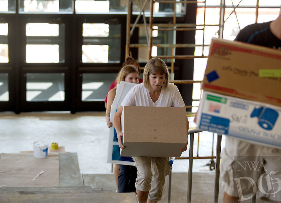 NWA Media/JASON IVESTER --08/21/2014--<br /> Carol Anderson and other volunteers help carry teachers' supplies on Thursday, Aug. 21, 2014, inside the new Joplin High School in Joplin, Mo. The school was originally scheduled to open with the rest of the school district on Monday, Aug. 25, but was pushed back to Tuesday, Sept. 2.