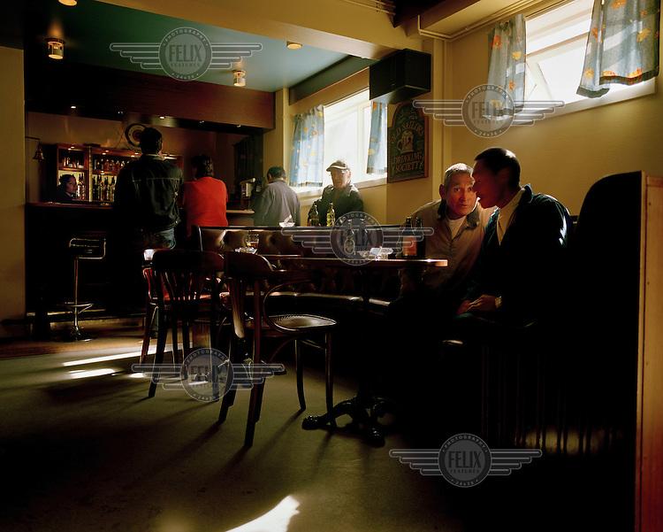 Men drink at a bar in Uummannaq.