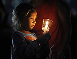 Londyn Arel, 7, of Enfield, is illuminated by the candles she is holding during a prayer given after the  annual processional at the Mount Carmel Society Thursday, July 30, in Enfield. The Italian Festival starts Friday at 5pm and runs through the weekend. (Jim Michaud / Journal Inquirer)