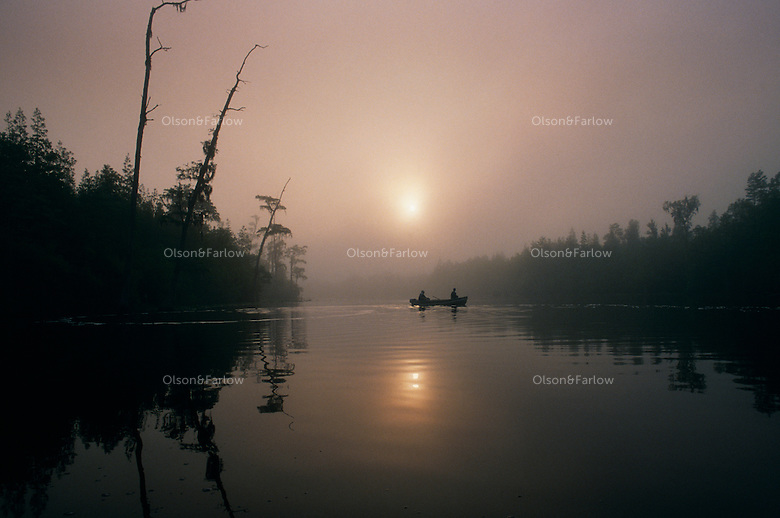 "Fishermen break the still waters of Billy's Lake on a foggy morning in the Okefenokee Wildlife Refuge. A mysterious aura surrounds the Okefenokee which means ""land of the trembling earth"" in a Native American language. <br /> Established in 1937, the Okefenokee National Wildlife Refuge protects the waters, wilderness and wildlife of the 438,000-acre Okefenokee Swamp."