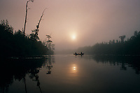 Fishermen break the still waters of Billy's Lake on a foggy morning in the Okefenokee Wildlife Refuge. A mysterious aura surrounds the Okefenokee which means &quot;land of the trembling earth&quot; in a Native American language. <br /> Established in 1937, the Okefenokee National Wildlife Refuge protects the waters, wilderness and wildlife of the 438,000-acre Okefenokee Swamp.
