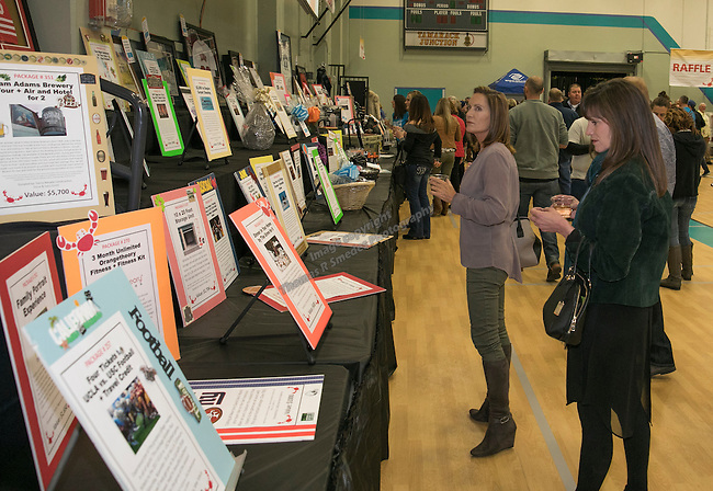 Kelly Werner and Kelly Horgan look at the auction items during the Jack T. Reviglio Cioppino Feed & Auction at the Donald W. Reynolds Facility in Reno on Saturday, February 25, 2017.