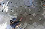 A woman casts lids for cement water containers in the Cambodian village of Bour.