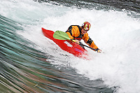 Andrew Jobe paddles a whitewater kayak through a wave on the Kananaskis River, Kananaskis County, Alberta, Canada