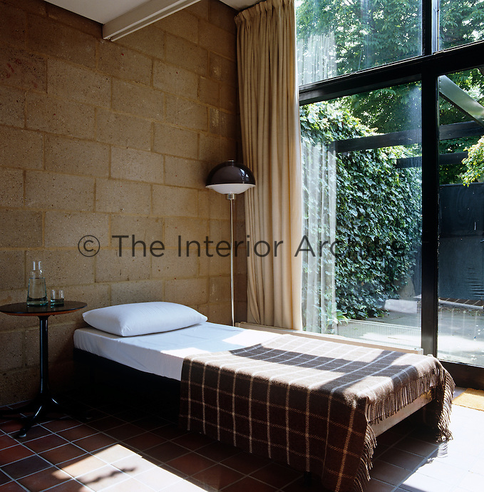 The guest bedroom has a simple exposed brick wall, tiled floor and a view of the rear garden