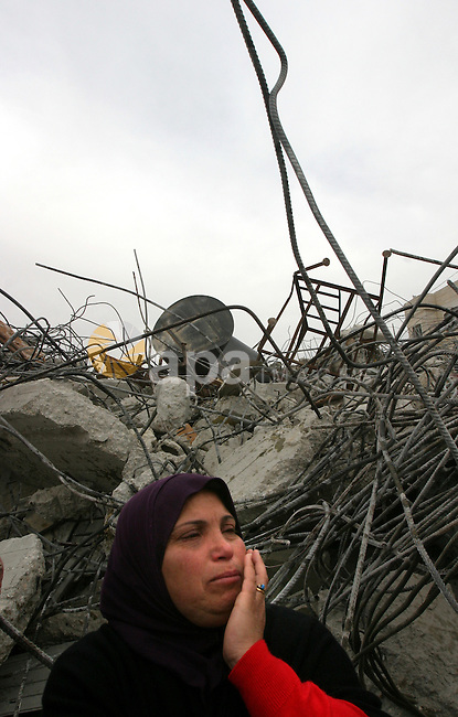 A Palestinian woman reacts after Israeli bulldozers demolished her family house in the Arab east Jerusalem neighborhood of Beit Hanina on February 5, 2013. Palestinian homes built without a construction permit are often demolished by order of the Jerusalem municipality. Photo by Mahfouz Abu Turk