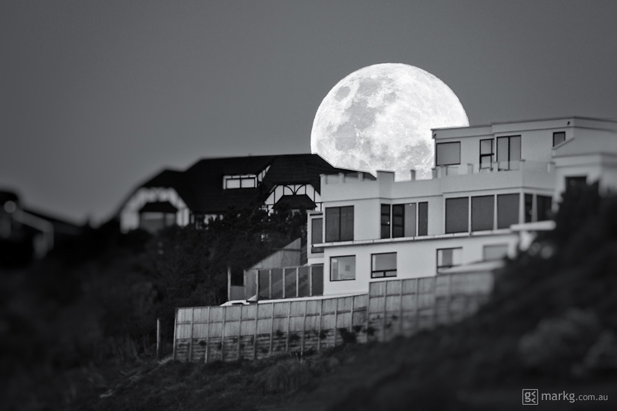 A full moon rises behind houses on the Maupuia ridge in Wellington, New Zealand