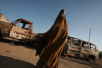 A  Somali woman walks in front of vehicles destroyed by a suicide bombing in Baidoa, Somalia on Wednesday Dec 27 2006.. the attack was on late September 2006 with the intent of killing the TFG ( transitional federal government )