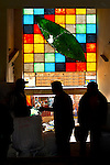 A symbolic coca leaf centers a colorful glass window above silhouetted men buying and selling 50 pound bags of coca leafs in the Villa Fatima Coca Market in La Paz, the largest legal coca market in Bolivia.