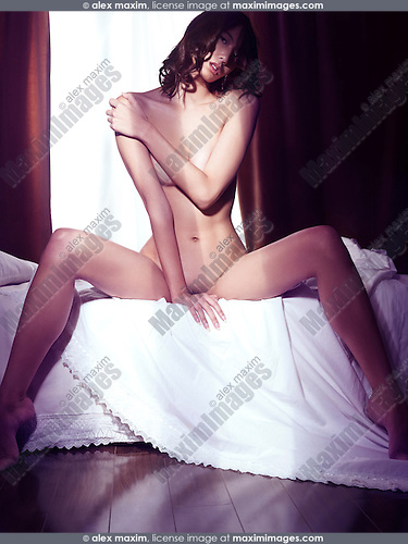 Artistic portrait of a beautiful nude asian woman sitting naked on a bed in dramatic light