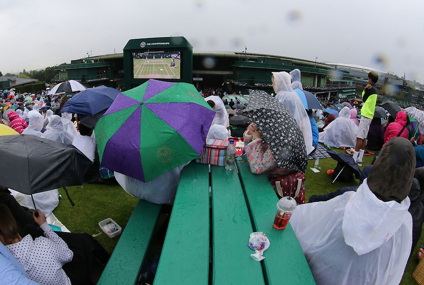 Fans shelter under umbrellas as rain delays the start of play on day six of the Wimbledon<br /> <br /> Photographer Kieran Galvin/CameraSport<br /> <br /> Tennis - Wimbledon Lawn Tennis Championships - Day 6 Saturday 28th June 2014 -  All England Lawn Tennis and Croquet Club - Wimbledon - London - England<br /> <br /> &copy; CameraSport - 43 Linden Ave. Countesthorpe. Leicester. England. LE8 5PG - Tel: +44 (0) 116 277 4147 - admin@camerasport.com - www.camerasport.com.