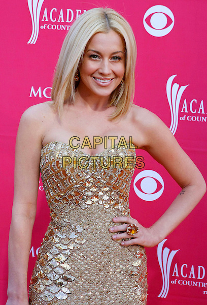 KELLIE PICKLER.44th Annual Academy Of Country Music Awards held at the MGM Grand Garden Arena, Las Vegas, Nevada, USA..April 5th, 2009.half length gold strapless dress ring metallic clutch bag scales hand on hip .CAP/ADM/MJT.© MJT/AdMedia/Capital Pictures.