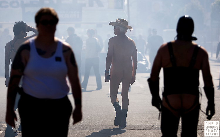 Early goers at the Folsom Street Fair, the world's largest leather event, walk through barbeque smoke in downtown San Francisco on Sunday, September 28, 2008.  (Christopher McGuire)