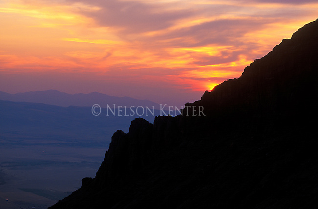 "The sun sets behind a rocky ridge on ""The helmet"" in the Madison Mountain Range near Ennis, Montana"