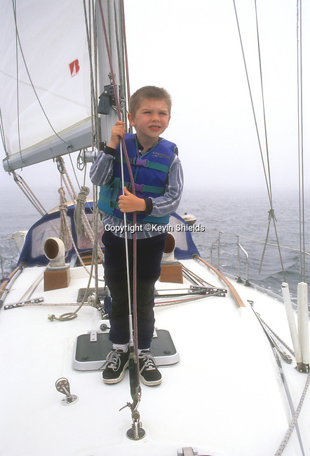 Boy on the foredeck of a sailboat under sail off the coast of Maine, USA
