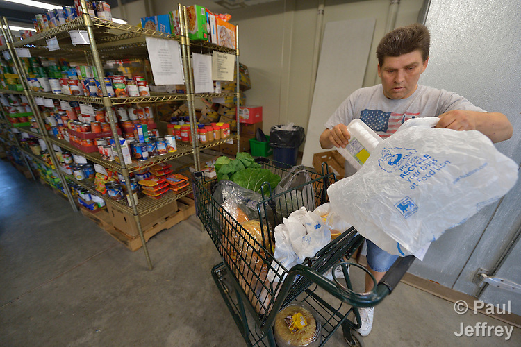Bill Rickrode, a volunteer, assembles a family food package in the Food Pantry of Urban Ministries of Wake County in Raleigh, North Carolina.